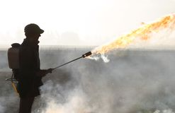 The fire starter. Farm hand showing off flame thrower used for lighting stubble/grass fires for a burn off on farmland in Canterbury, New Zealand royalty free stock images