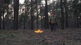 Fire starts in the forest. Arson in park. Setting fire to nature, flora, fauna. Boy looking around while standing in. Careless handling of the fire in the nature stock video
