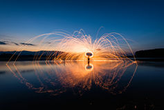 Fire steel wool in the lake at sunrise . Stock Photography