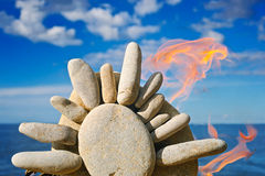 Fire and the stone sun. The stone symbol of the sun burns at the dark blue sea Royalty Free Stock Image