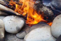 Fire stones flame tree sand. The flame of the burning wood on the stones stock photos