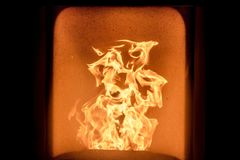 Fire in stove. An orange flame in a warm and black fireplace Royalty Free Stock Photos