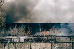 Fire and strong smoke in burning industrial building, danger accident disaster with damage from fire. Concept Royalty Free Stock Images