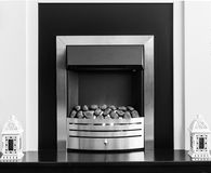 Fire surround black and white. Black and white fire surround with  ornamental lanterns at the sides, flower vases on the top of the fire place, with wall paper Stock Photos