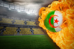 Fire surrounding algeria flag football. Composite image of fire surrounding algeria flag football against large football stadium with lights Royalty Free Stock Image
