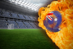 Fire surrounding australia flag football. Composite image of fire surrounding australia flag football against vast football stadium with fans in blue Royalty Free Stock Photos