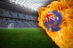 Fire surrounding australia flag football. Composite image of fire surrounding australia flag football against vast football stadium with fans in blue Stock Image