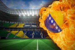 Fire surrounding bosnia flag football. Composite image of fire surrounding bosnia flag football against large football stadium with brasilian fans Stock Photography