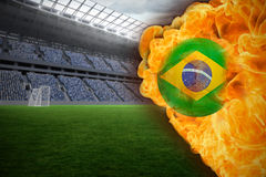 Fire surrounding brasil flag football. Composite image of fire surrounding brasil flag football against vast football stadium with fans in blue Royalty Free Stock Photo