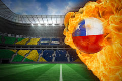 Fire surrounding chile flag football. Composite image of fire surrounding chile flag football against large football stadium with brasilian fans Royalty Free Stock Images