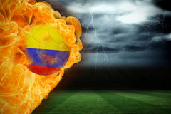 Fire surrounding colombia flag football. Composite image of fire surrounding colombia flag football against football pitch under stormy sky Stock Photo