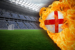 Fire surrounding england flag football. Composite image of fire surrounding england flag football against vast football stadium with fans in blue Royalty Free Stock Image