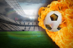 Fire surrounding football. Composite image of fire surrounding football against large football stadium with lights Stock Images