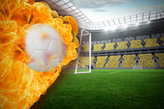 Fire surrounding football. Composite image of fire surrounding football against vast football stadium with fans in yellow Royalty Free Stock Photos