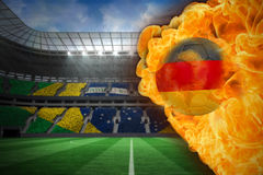 Fire surrounding germany flag football. Composite image of fire surrounding germany flag football against large football stadium with brasilian fans Royalty Free Stock Image