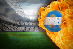 Fire surrounding honduras flag football. Composite image of fire surrounding honduras flag football against large football stadium with lights Stock Images