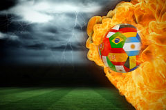 Fire surrounding international flag football. Composite image of fire surrounding international flag football against football pitch under stormy sky Royalty Free Stock Image