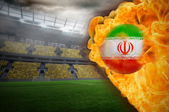 Fire surrounding iran flag football. Composite image of fire surrounding iran flag football against large football stadium with lights Royalty Free Stock Photo