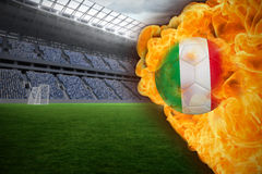 Fire surrounding italy flag football. Composite image of fire surrounding italy flag football against vast football stadium with fans in blue Royalty Free Stock Images