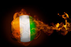 Fire surrounding ivory coast ball. Composite image of fire surrounding ivory coast ball against black Stock Photo