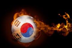 Fire surrounding korea republic ball. Composite image of fire surrounding korea republic ball against black Stock Images