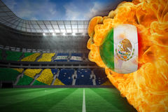 Fire surrounding mexico flag football. Composite image of fire surrounding mexico flag football against large football stadium with brasilian fans Stock Photos