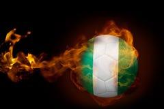 Fire surrounding nigeria ball. Composite image of fire surrounding nigeria ball against black Stock Images