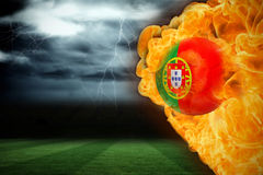 Fire surrounding portugal flag football. Composite image of fire surrounding portugal flag football against football pitch under stormy sky Stock Image