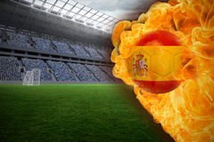 Fire surrounding spain flag football. Composite image of fire surrounding spain flag football against vast football stadium with fans in blue Royalty Free Stock Images