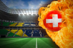 Fire surrounding switzerland flag football. Composite image of fire surrounding switzerland flag football against large football stadium with brasilian fans Stock Photography