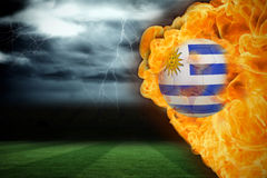 Fire surrounding uruguay flag football. Composite image of fire surrounding uruguay flag football against football pitch under stormy sky Stock Photos