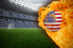 Fire surrounding usa flag football. Composite image of fire surrounding usa flag football against vast football stadium with fans in blue Royalty Free Stock Photo