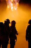 Fire teamwork. Firefighters fight a blaze as a team using a water hose Stock Photography