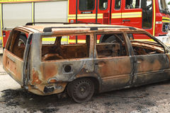 Fire tender at a car fire burnt out vehicle. Fire engine at the scene of a car fire. Burnt out car Stock Photography