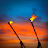 Fire torch at sunset sky with red clouds Stock Photo