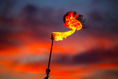 Fire torch at sunset sky with red clouds Stock Images