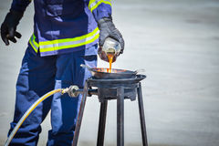 Fire trainer teach pouring oil into pan flames for conflagration Royalty Free Stock Photos