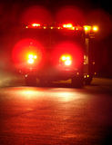 Fire Truck with Emergency Lights Driving at Night. Speeding fire truck with flashing emergency warning lights driving fast to a disaster response scene on a Royalty Free Stock Image