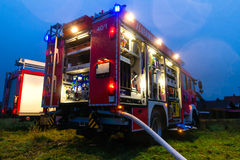 Fire truck with lights in deployment. Fire truck or engine with flashing lights, lighting and hose in dusk, ready for deployment Stock Images