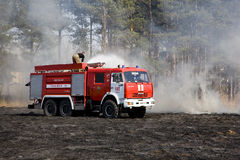 The fire truck extinguishes a fire. The fire crew extinguishes a burning grass in the settlement  Thresholds on May 04, 2013 Royalty Free Stock Images