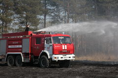 The fire truck extinguishes a fire. The fire crew extinguishes a burning grass in the settlement  Thresholds on May 04, 2013 Stock Image