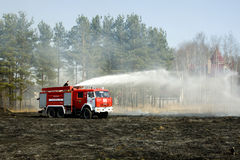 The fire truck extinguishes a fire. The fire crew extinguishes a burning grass in the settlement Thresholds on May 04, 2013 stock photos