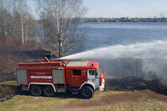 The fire truck extinguishes a fire. The fire crew extinguishes a burning grass in the settlement Thresholds on May 04, 2013 royalty free stock photo