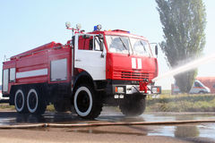 The fire truck extinguishes the lit-up plane Stock Photo