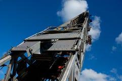 Fire Truck Ladder. Steel fire truck ladder leading up into blue sky Stock Photo