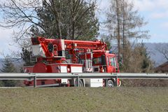 Fire truck with a ladder moving on the highway. Rear view of specialized vehicles. Firefighters are going to call. Budget public royalty free stock image