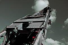Fire Truck Ladder into Steel Gray Sky. Steel fire truck ladder leading up into gray sky royalty free stock image