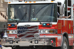 Fire truck in a  parade in small town America. Fire truck with an American flag in the grille and lights flashing in a summer parade in small town America Stock Photo