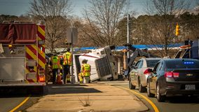 Carrboro NC, /US-March 10 2017:Fire truck and police cars with overturned logging truck. Fire truck, police cars and workers at site of highway accident with stock images