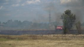 The fire truck is driving through the scorched field. A fire truck rides on a burning field to extinguish a summer fire stock video